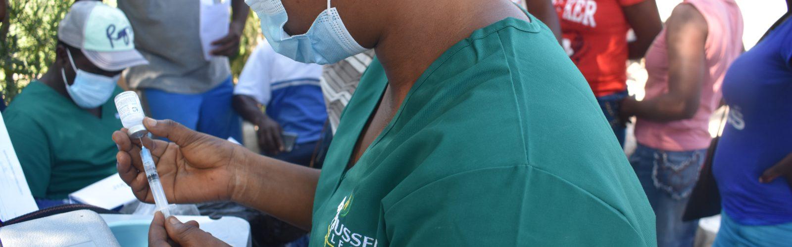HAS staff fills COVID vaccine syringe